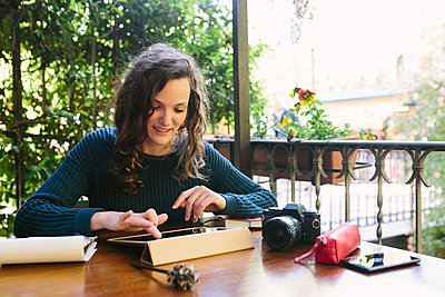 Young woman sitting on balcony, working with digital tablet - p300m1153926 by Boy photography