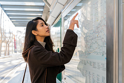Young woman looking at map at the tram stop - p300m2166182 by VITTA GALLERY