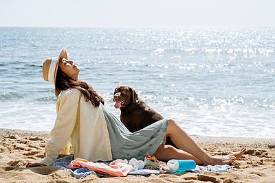 Mid adult woman relaxing by dog at beach during sunny day - p300m2281343 by VITTA GALLERY