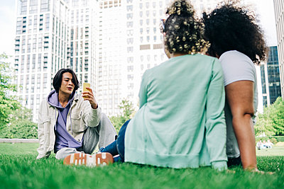 Man photographing female friends at park - p300m2293256 by Angel Santana Garcia