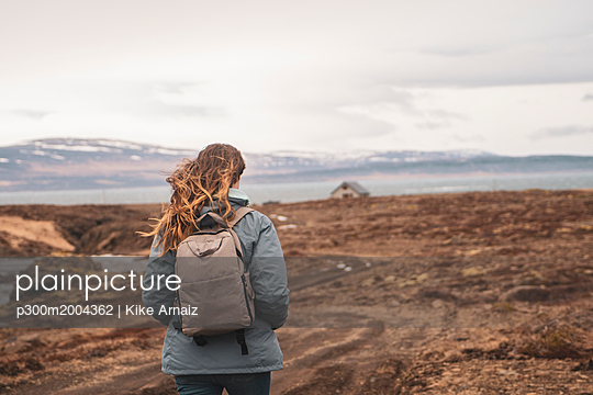 Iceland, back view of woman with backpack hiking in landscape - p300m2004362 von Kike Arnaiz