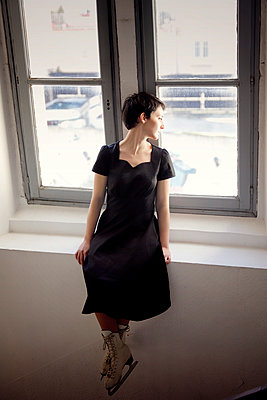 Woman in black dress and ice skates looking out of window - p1105m2244913 by Virginie Plauchut