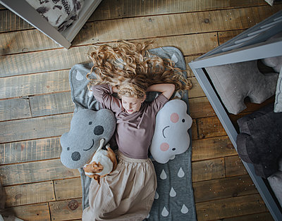 Girl lying on the floor with a dog and toys - p1414m1590599 by Dasha Pears