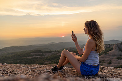 Spain, Catalonia, Sant Llorenc del Munt i l'Obac, woman taking pictures in the mountains with her smartphone - p300m2028691 von VITTA GALLERY