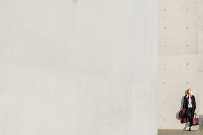 Blond businesswoman leaning on a concrete wall - p300m2154515 by Hernandez and Sorokina