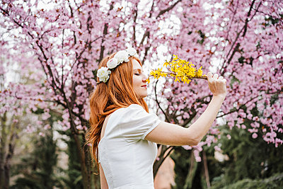 Beautiful woman smelling yellow flower while standing in front of almond tree at park - p300m2274608 by Eva Blanco