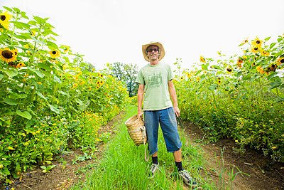 Caucasian farmer standing in rows of sunflowers - p555m1408544 by Jed Share/Kaoru Share