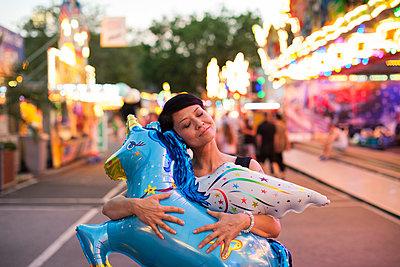 Junge Frau auf dem Jahrmarkt umarmt einen Luftballon - p586m939372 von Kniel Synnatzschke