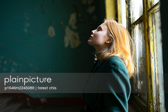Sad teenage girl with red hair in the staircase - p1646m2245089 by Slava Chistyakov