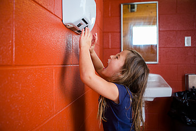 Side view of cute girl screaming over hand dryer while standing against wall in bathroom - p1166m2068080 by Cavan Images
