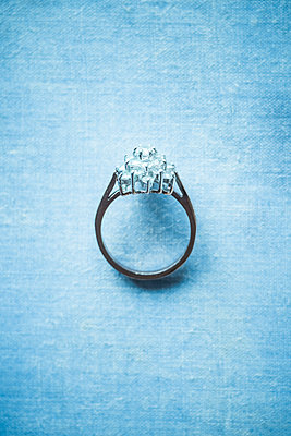A ring with many diamonds on a pale blue slightly out of focus background - p1302m2089438 by Richard Nixon