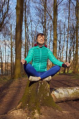 Sportliche Frau meditiert auf einem Baumstumpf - p1491m2176009 von Jessica Prautzsch