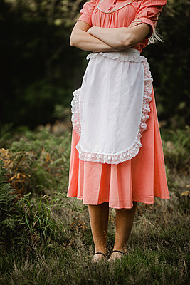 Young woman in pink dress and white apron - p1628m2212003 by Lorraine Fitch