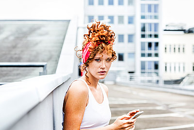 Portrait of redheaded woman holding cell phone - p300m1505899 by Jo Kirchherr
