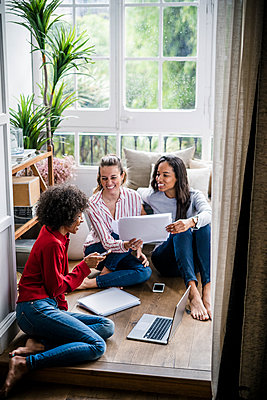 Three friends at home, living together - p300m2079819 von Giorgio Fochesato