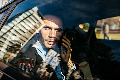 Man sitting on back seat of a car talking on cell phone - p300m2080601 by Josep Rovirosa