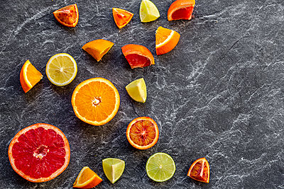Sliced citrus fruits on slate - p300m2083803 by Sandra Roesch