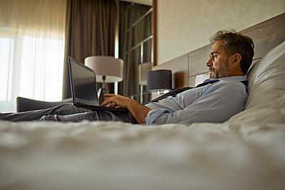 Businessman lying on bed in hotel room using laptop - p300m2170980 by Zeljko Dangubic
