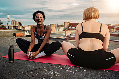 Cheerful woman with female friend exercising on rooftop - p426m2233636 by Maskot