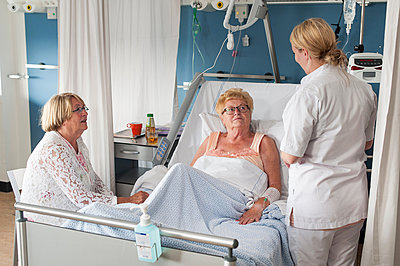 Nurse and visitor tending to patient in hospital bed - p429m1198071 by Arno Masse