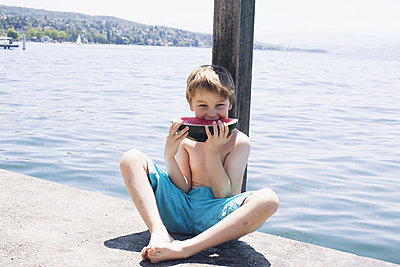 Boy eating watermelon on dock - p624m1174329 by Anne-Sophie Bost