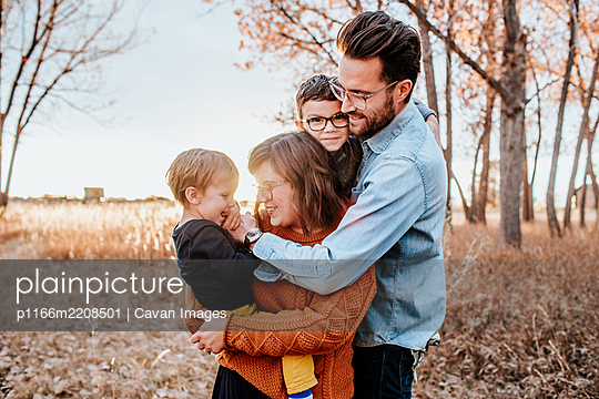Fashionable young family hugging in a field on a cool autumn evening - p1166m2208501 by Cavan Images