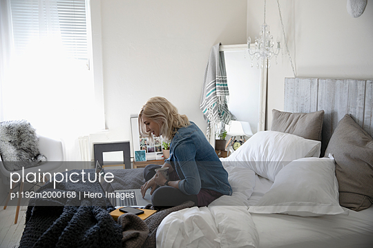 Young woman drinking coffee and using laptop on bed - p1192m2000168 by Hero Images