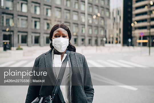 Portrait of female entrepreneur on street in city during COVID-19 - p426m2270336 by Maskot