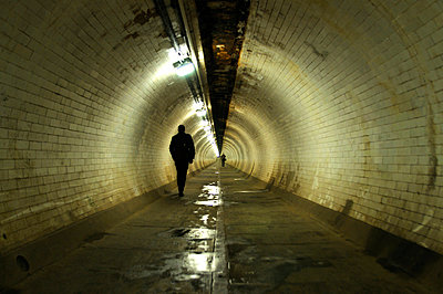 Silhouetted male figure walking through tunnel - p1072m829323 by Neville Mountford-Hoare