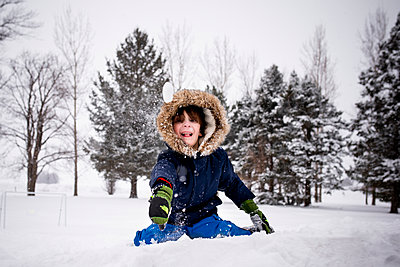 Small Young Boy Throwing A Snow Ball Into The Camera - p1166m2095507 by Cavan Images