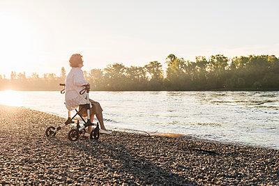 Pensive senior woman sitting on her wheeled walker at riverside - p300m1459856 by Uwe Umstätter