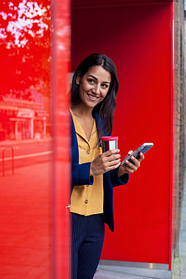 Young businesswoman with reusable coffee cup and smartphone , leaning on wall - p300m2159884 by LOUIS CHRISTIAN