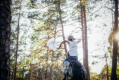Rear view of father with backpack carrying daughter on shoulder in forest - p426m2213323 by Maskot