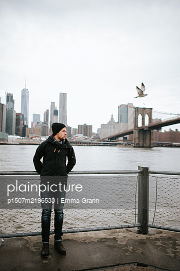 Man waiting on the waterfront, Brooklyn Bridge in the background - p1507m2196533 by Emma Grann