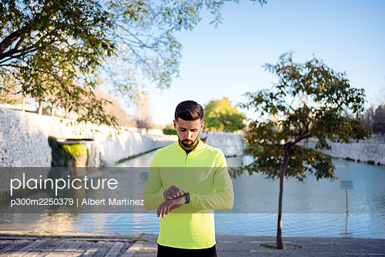 Male athlete checking time while standing against lake at park - p300m2250379 by Albert Martínez