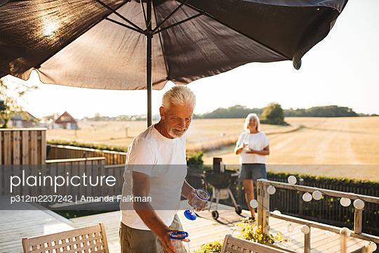 Man standing by table in garden - p312m2237242 by Amanda Falkman