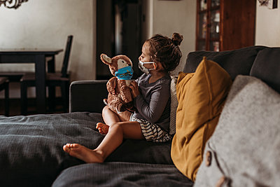 Side view of preschool age girl with mask on cuddling masked toy - p1166m2207783 by Cavan Images