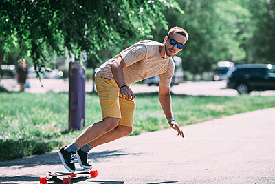 Young man riding skateboard on the street - p300m1505282 by Vasily Pindyurin