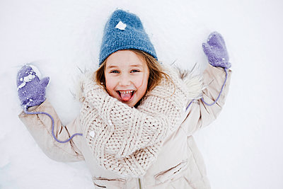 Cheerful girl sticking out tongue lying on snow during vacations - p300m2256091 by Katharina Mikhrin