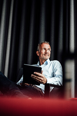 Smiling male business professional looking away while holding digital tablet on armchair in office cafeteria - p300m2266321 by Gustafsson