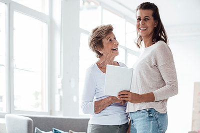 Cheerful senior woman looking at granddaughter holding digital tablet at home - p300m2276846 by Gustafsson