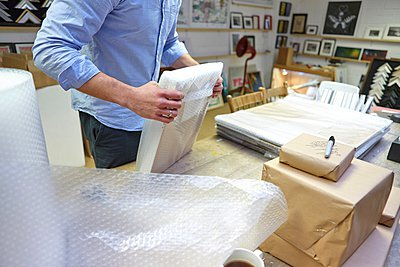 Man bubble wrapping picture frame on table in picture framers workshop - p429m1021703f by Janie Airey