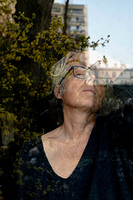 Grey-haired woman with closed eyes at the window - p445m2173642 by Marie Docher