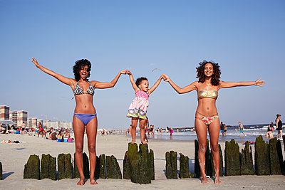 Mixed race women and girl holding hands at beach - p555m1479555 by Granger Wootz