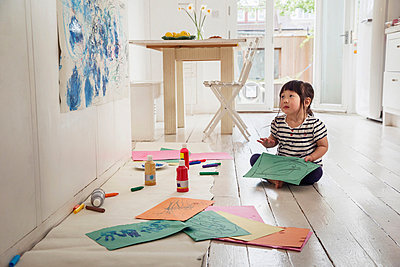 Female toddler sitting on floor with drawings - p924m821469f by Igor Emmerich