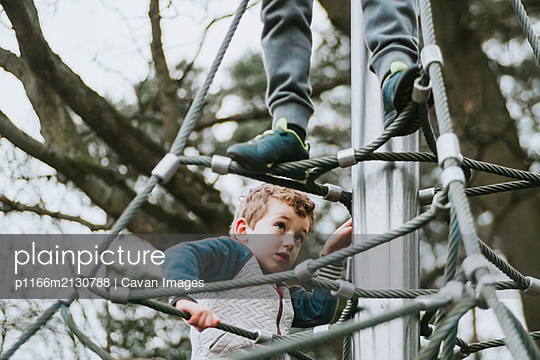 Low angle view of brothers climbing up jungle gym - p1166m2130788 by Cavan Images