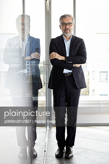 Portrait of confident businessman standing in office - p300m2012957 von Rainer Berg