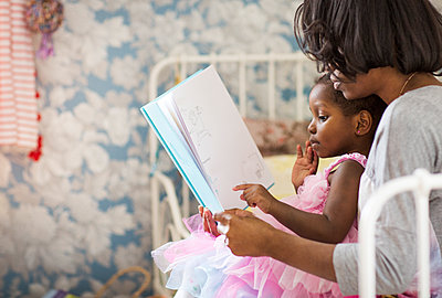 Girl pointing at picture book while sitting with mother in bedroom - p1166m1140360 by Cavan Images