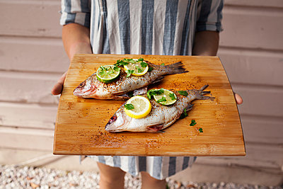 Midsection of woman holding raw fish on cutting board - p1166m1163893 by Cavan Images