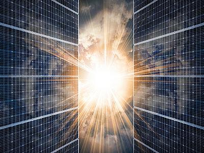 Sun shining through solar panels - p1427m2202145 by Tetra Images